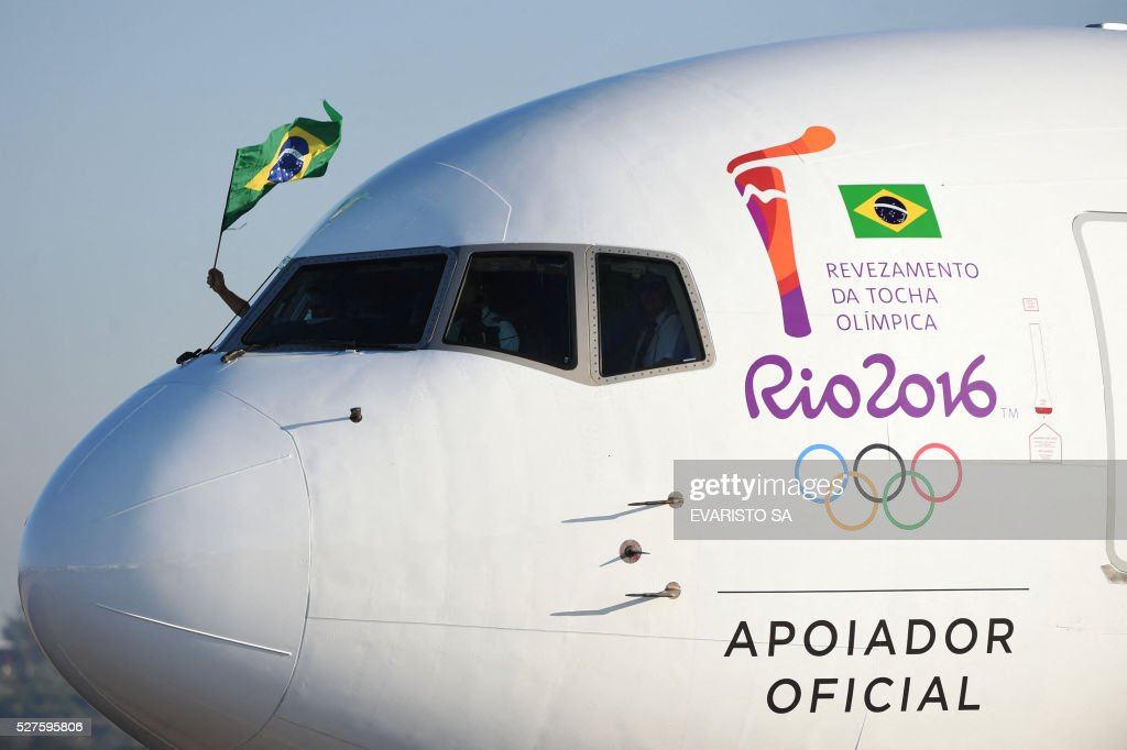 The Brazilian national flag is seen from the cockpit window of a LATAM Boeing 767-300ER aircraft in special Rio 2016 livery transporting the Olympic flame as it arrives in Brasilia from Geneva on May 3, 2016, beginning the flame's journey across the country before the start of the 2016 Olympic Games on August 5. The Olympic flame arrived in Brasilia May 3 aboard a flight from Geneva to embark on a procession across Brazil culminating in the opening ceremony of the 2016 Games in Rio de Janeiro. The torch will travel to more than 300 towns and cities carried by some 12,000 relay runners before arriving August 5 at the mythic Maracana stadium to kick off the first Olympics in South America. / AFP / EVARISTO SA