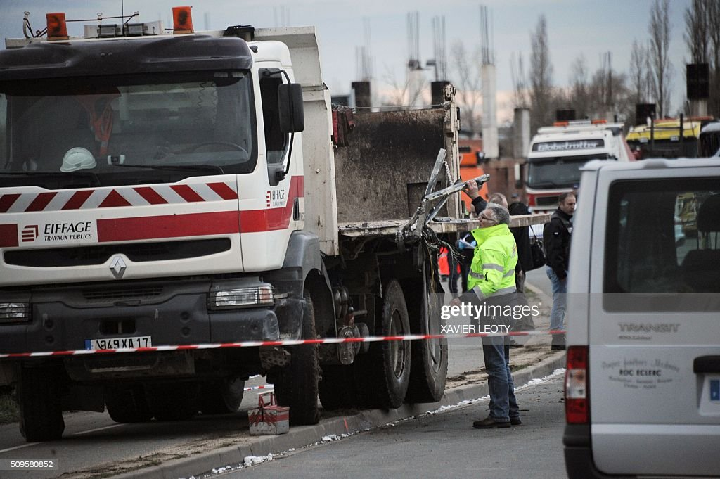 The breakdown mechanic stands next to the wreckage of a truck after it crashed into school bus in Rochefort on February 11, 2016, killing at least six children, police said, a day after another road accident involving a school bus left two youngsters dead. The head-on smash with a lorry carrying rubble came around 7:15 am (0615 GMT) in Rochefort in the western Charente-Maritime region. The school bus was carrying about 17 people, and three children suffered minor injuries in the accident, a police source said. / AFP / XAVIER LEOTY