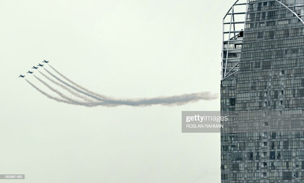 The Breitling jet team flies past Reflections at Keppel bay condominium as they perform an aerobatic display over Sentosa Island, off Singapore on March 9, 2013. The Breitling jet team is in Singapore as part of their Asian tour.
