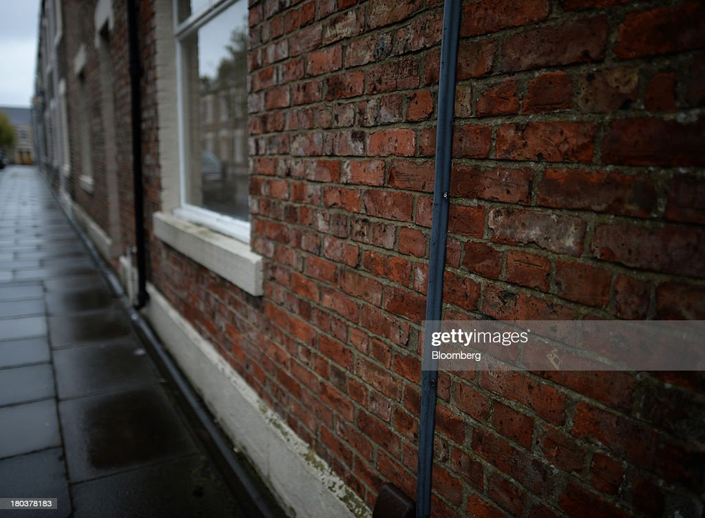 The brickwork of a residential home stands exposed on a row of terraced properties in Newcastle-upon-Tyne, U.K., on Wednesday, Sept. 11, 2013. U.K. house prices rose for a seventh month in August and will probably continue to increase through the rest of the year, according to a report by Halifax. Photographer: Nigel Roddis/Bloomberg via Getty Images