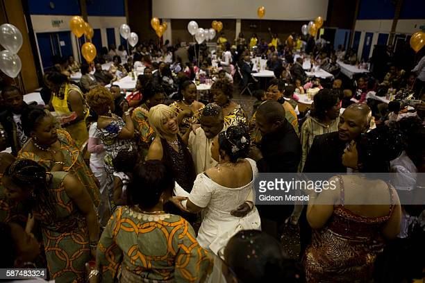 The bride and groom embrace a friend during the first dance as a Congolese wedding party takes place at a community hall in Hackney The bride and...