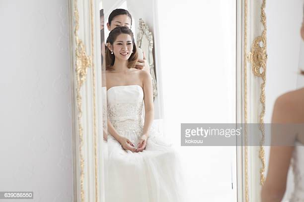 The bride is reflected in the mirror.