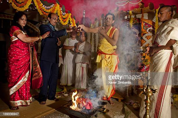 The bride's mother and father performing Ganesh Havan before the Simanti poojan ceremony at The Art of living International centre Ashram on June 19...