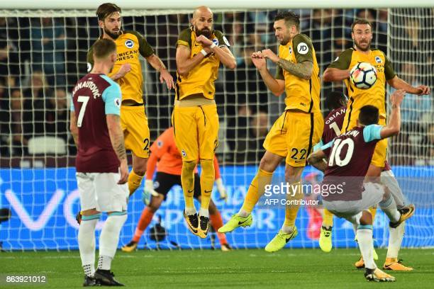 The Brighton wall jumps as West Ham United's Argentinian midfielder Manuel Lanzini takes a freekick during the English Premier League football match...