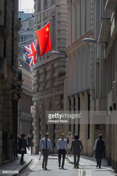 The British and Chinese flags hanging above Londoners in a narrow medieval street in the capital's oldest financial district aka The Square Mile on...
