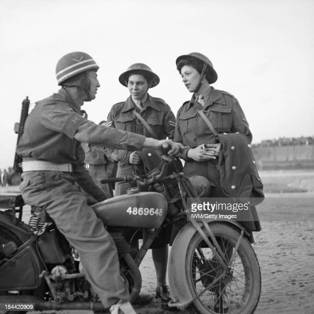 The British Army In Normandy 1944 L/Cpl E Martin of the Corps of Military Police sits astride his motorcycle and chats to Cpl Joyce Collins and L/Cpl...