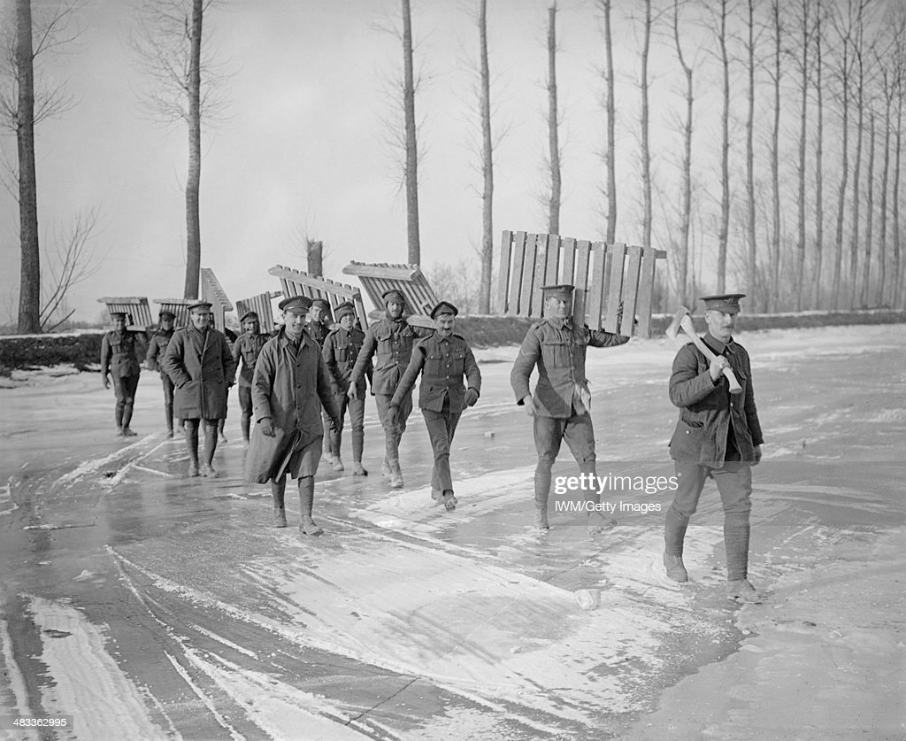 The British Army On The Western Front, March 1917, Members of a Royal Garrison Artillery working party carrying duck-boards across the frozen Somme canal at Frise, March 1917.