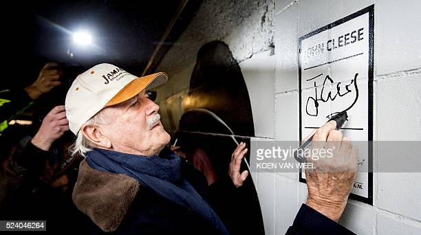 The British comedian and actor John Cleese signs on the wall next to a drawing by graffiti artists refering to a Monty Python's sketch during the...