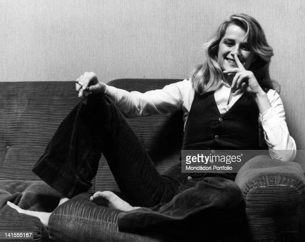 The British film actress Charlotte Rampling smiles sitting on a sofa Milan 1974
