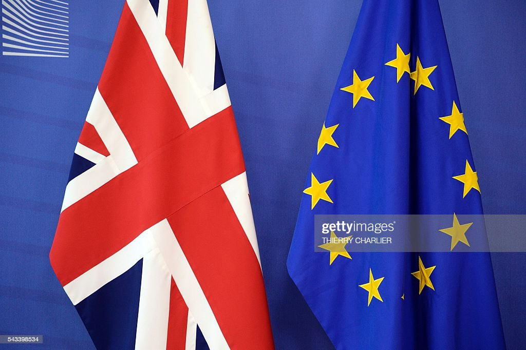 The British flag (L) is seen along with the European Union flag (R) at the European Union Commission headquarters in Brussels on June 28, 2016. / AFP / THIERRY