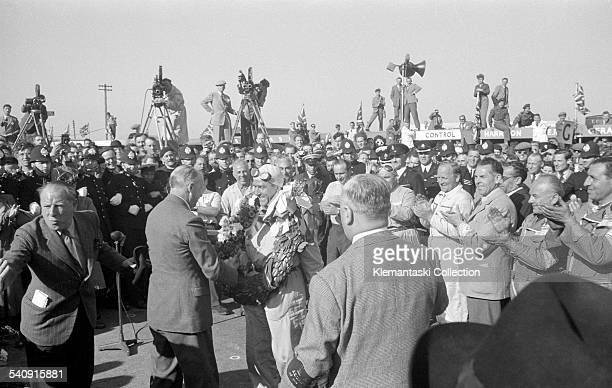 The British Grand Prix Silverstone May 13 1950 'Nino' Farina is all smiles as he receives his trophy with his victory garland already around his neck