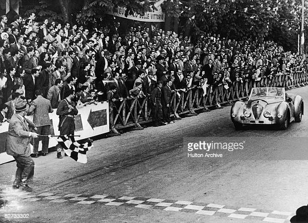 The British Healey car driven by Geoffrey Healey and T H Wisdom arrives at Brescia to win the touring car class of the Mille Miglia with a record...