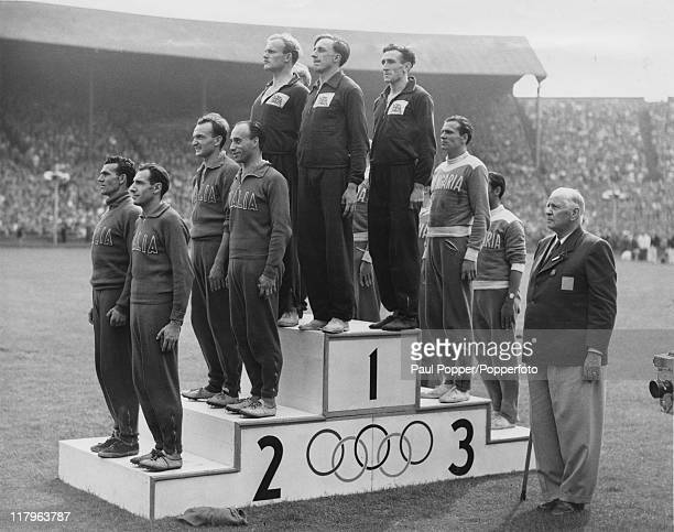 The British Men's 4 x 100 Metres Relay team on the winners podium at Wembley Stadium with Italy second and Hungary third after the disqualification...