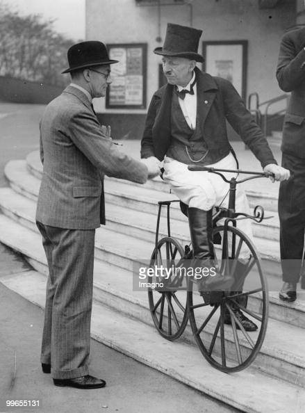 The British motor tycoon Lord Nuffield talks to a participant of the engine and bike exhibition at Earls Court in London who just arrived with his...