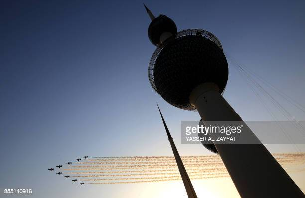 The British Royal Air Force's aerobatic team the 'Red Arrows' performs aerial manoeuvres near Kuwait's Towers during an airshow in Kuwait City on...