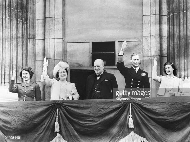 The British sovereigns and their daughters around the British Prime Minister Winston CHURCHILL greeting the crowd from the balcony of Buckingham...