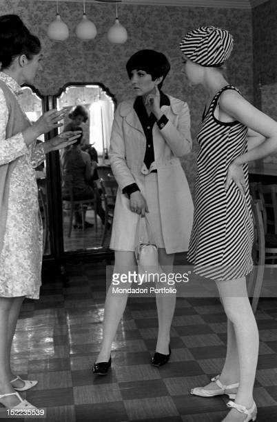 The British stylist Mary Quant talking with a woman Beside her a model wearing a striped minidress with a matched beret London 1960s