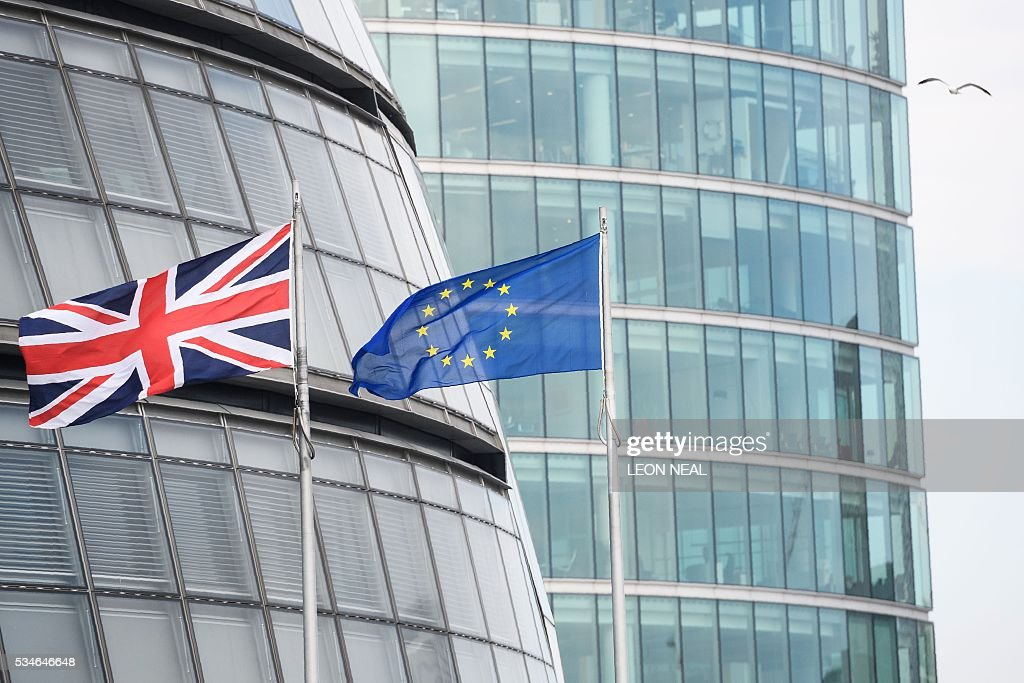 The British Union flag (L) and the European Union (EU) flag fly side-by-side outside City Hall, the headquarters of the Greater London Authority, in central London, on 27 May 2016. Britain could be plunged into a year-long recession and lose hundreds of thousands of jobs if it voted to leave the EU next in the June 23 referendum, the government warned earlier this week, in a report critics dismissed as 'deeply biased'. / AFP / LEON