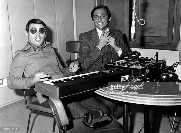 The broadcast presenters Renzo Arbore and Gianni Boncompagni sitting before a keyboard and other instruments during Alto Gradimento the radio...