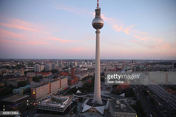 The broadcast tower at Alexanderplatz looms over the city center at sunset on June 18 2014 in Berlin Germany Alexanderplatz a crossing point of...