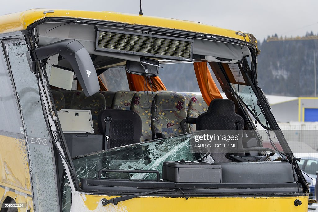 The broken windshield of a damaged school bus is pictured as the bus is towed away in Pontarlier, after it crashed on a motorway in Montbenoît, eastern France, on February 10, 2016. Two persons were killed and four slightly injured, after the school bus went off the road presumably due to bad weather conditions, according to the police. The accident occurred at around 7:30 a.m. on Wednesday, when it was on its way to the Lucie Aubrac college in the Doubs region. / AFP / FABRICE COFFRINI