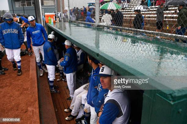 The Broomfield Eagles take shelter from the rain in their dugout after the Colorado State 5A championship game against the Rocky Mountain Lobos was...