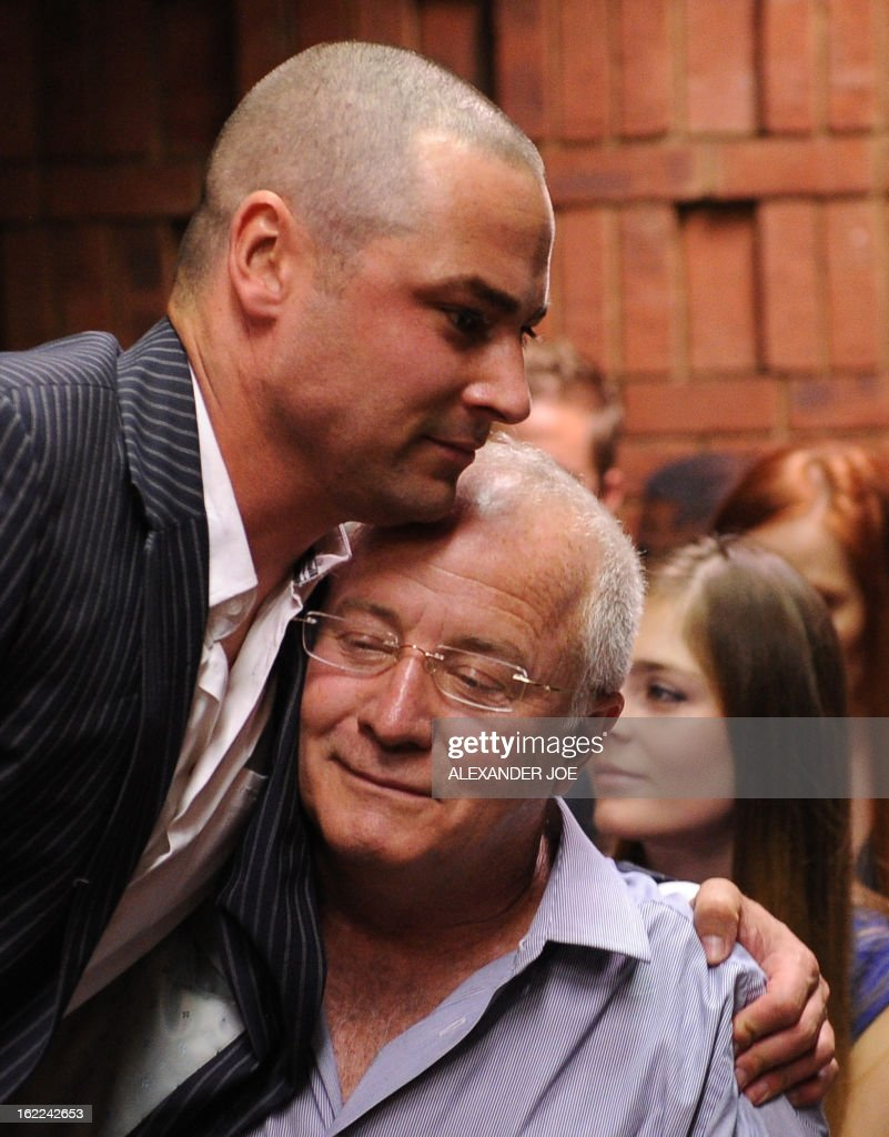 The brother and the father of South African Olympic sprinter Oscar Pistorius Carl and Henke hug on February 21 2013 at the Magistrate Court in...
