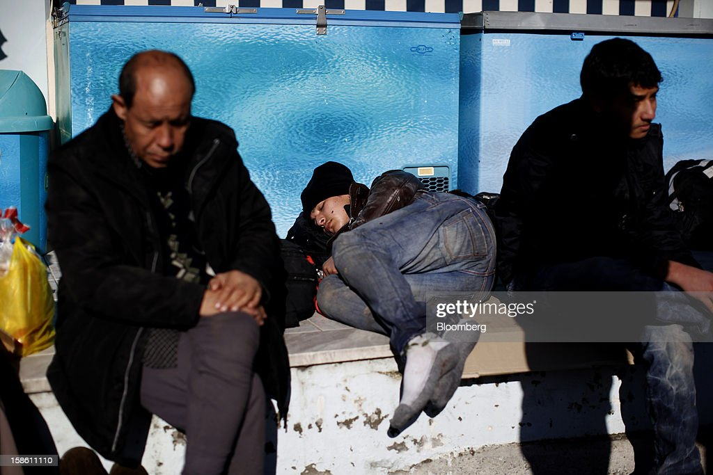 The brother of Afghan immigrant Mustafa, center, rests with members of his family in front of a store hours after they landed on the island of Lesbos' northern coast in Mantamados, Greece, on Saturday, Dec. 8, 2012. In recent months, Lesbos has become a hot spot for migrants as Greece struggles to cope with waves of refugees from Middle Eastern conflict even as it reels from economic crisis at home. Photographer: Kostas Tsironis/Bloomberg via Getty Images