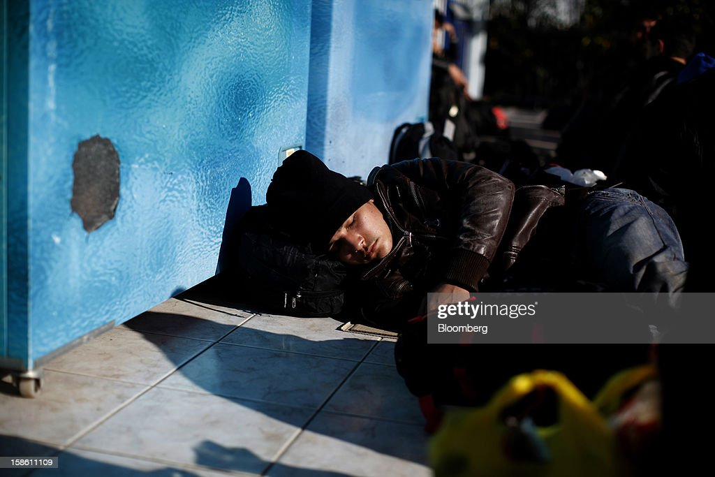 The brother of Afghan immigrant Mustafa rests in front of a store hours after they landed on the island of Lesbos' northern coast in Mantamados, Greece, on Saturday, Dec. 8, 2012. In recent months, Lesbos has become a hot spot for migrants as Greece struggles to cope with waves of refugees from Middle Eastern conflict even as it reels from economic crisis at home. Photographer: Kostas Tsironis/Bloomberg via Getty Images