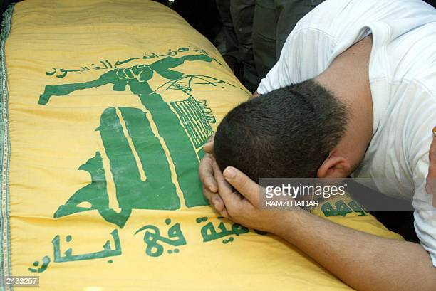 The brother of Hezbollah activist Ammar Hammoud weeps over his coffin draped with the Shiite Muslim group's yellow flag during his funeral following...
