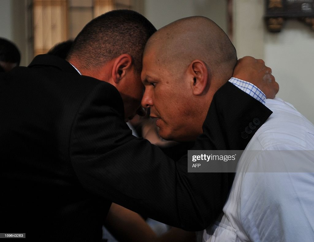 The brother of late Colombian goalkeeper Miguel Calero, Milton (R), is embraced by Colombian goalkeeper Farid Mondragon, during a mass in honour of Miguel, in Ginebra, Valle del Cauca department, Colombia, on January, 17, 2013. Calero, former goalkeeper of Mexico's Club Pachuca, died on December 4, 2012 in Mexico, after suffering brain death caused by thrombosis. Half of his ashes were left at the headquarters of pachuca in Mexico while the other half were brought to be buried in Colombia. AFP PHOTO/Luis ROBAYO