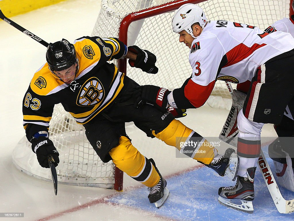 The Bruins' Brad Marchand gets pushed into the net by the Senators' Marc Methot as he came in for a loose puck in second period action as the Boston Bruins took on the Ottawa Senators at TD Garden.