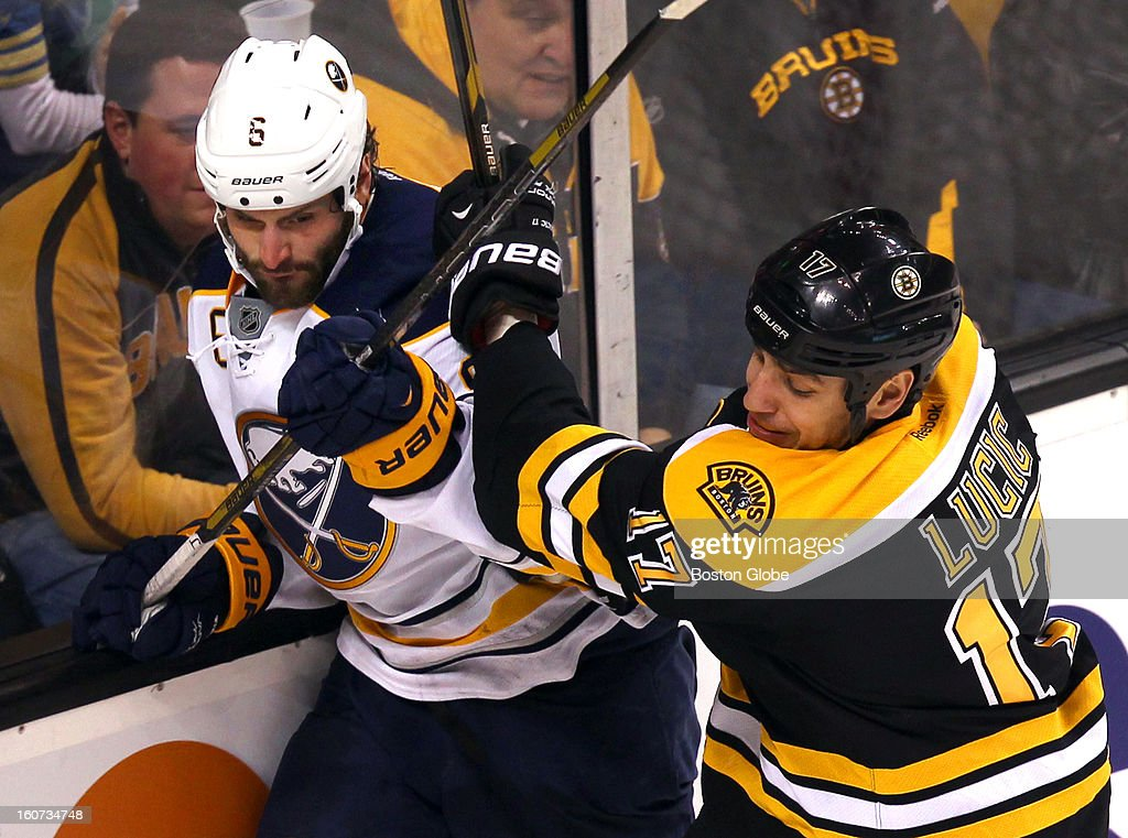 The Bruins' Milan Lucic checks Sabres player Mike Weber into the boards in the second period as the Boston Bruins hosted the Buffalo Sabres in an NHL regular season game at TD Garden.