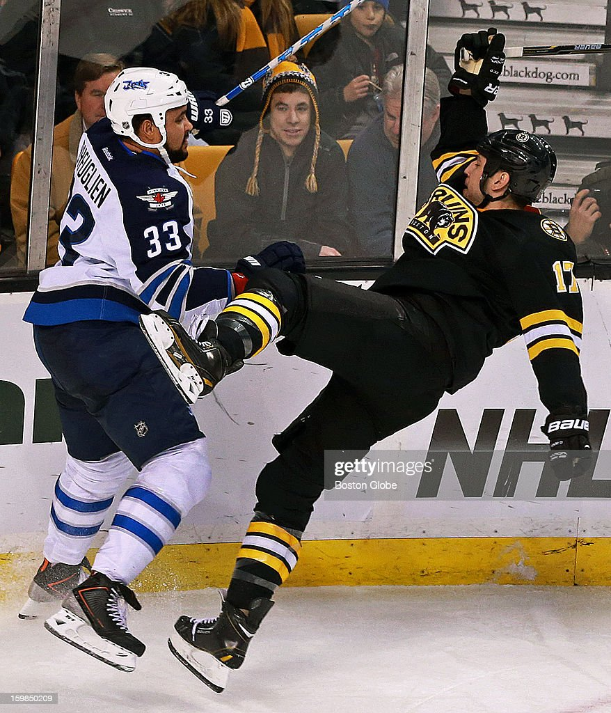 The Bruins' Milan Lucic, right, gets the worst of this second period collision with the Jets' Dustin Byfuglien, left, as he leaves his feet and hits the ice. The Boston Bruins hosted the Winnipeg Jets in an NHL regular season game at the TD Garden.
