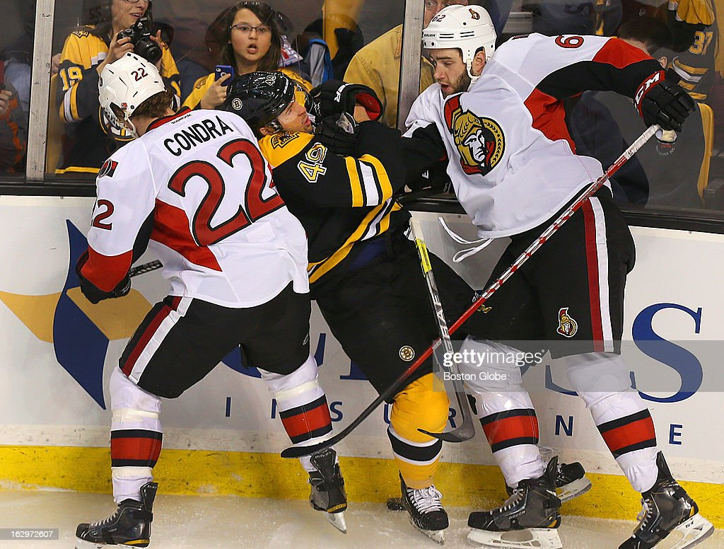 The Bruins' Rich Peverley is sandwiched between the Senators' Erik Condra, left, and Eric Gryba in first period action as the Boston Bruins took on the Ottawa Senators at TD Garden.