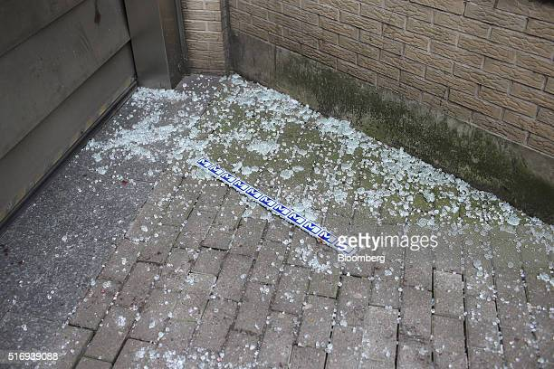 The Brussels metro railway logo sits on the ground amongst glass fragments and drops of blood outside a shuttered entrance to Maelbeek metro station...