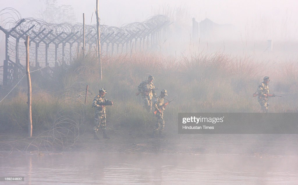 The BSF troops patrolling in thick fog on a boat in the riverine area along the border with Pakistan in Ajnala sector on January 10, 2013 about 45 KMS from Amritsar, India. The situation between the two countries become tense after the Killing of two Indian soldiers by infiltrating Pakistani troops in Jammu and Kashmir.