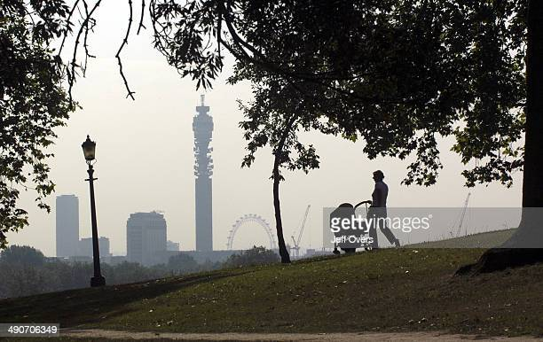 The BT Tower and the Millennium Wheel can be seen on the skyline in the distance as a woman takes a baby out for a walk in a pram framed by trees and...
