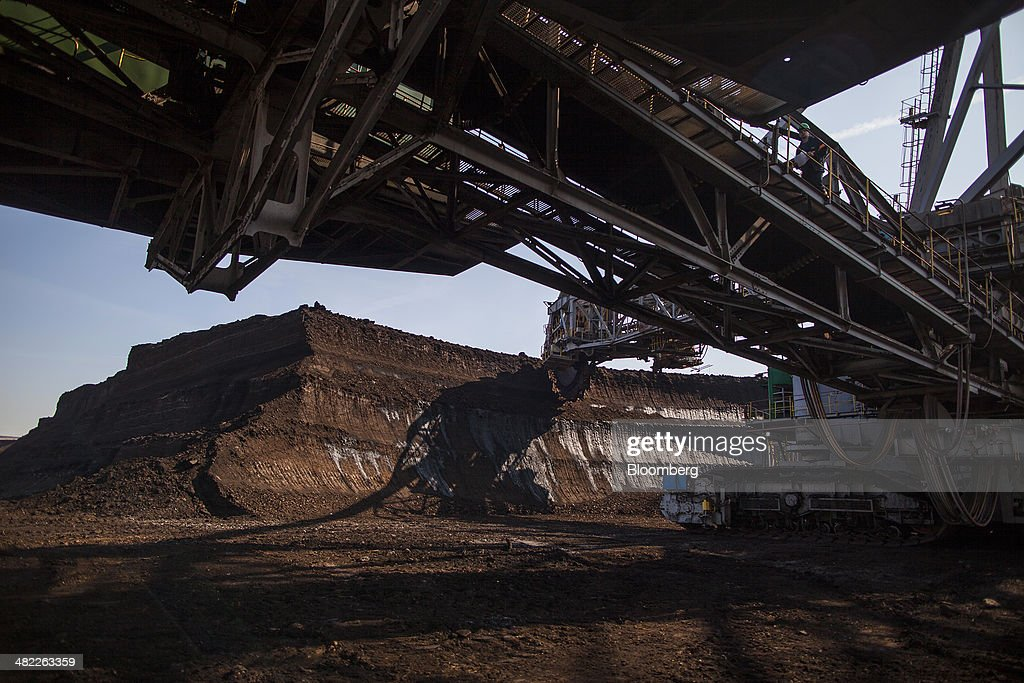 The bucket wheels of a giant excavator cut into the earth during lignite, also known as brown coal, digging operations at the open pit mine operated by PGE Elektrownia Belchatow SA near Belchatow, Poland, on Wednesday, April 2, 2014. Polish power prices are set to stay above German contracts through 2015, reversing a historic discount, as the cost of keeping plants open in the eastern European nation is factored in, according to Vattenfall AB. Photographer: Bartek Sadowski/Bloomberg via Getty Images