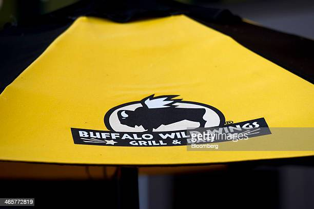 The Buffalo Wild Wings Inc logo is displayed on an umbrella of a restaurant in Dublin California US on Saturday Jan 25 2014 Buffalo Wild Wings Inc is...