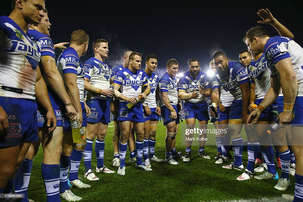 The Bulldogs team prepare to sing their team song in front of the crowd on the hill as they celebrate victory during the round 16 NRL match between the Canterbury Bulldogs and the Melbourne Storm at Belmore Sports Ground on June 29, 2015 in Sydney, Australia.