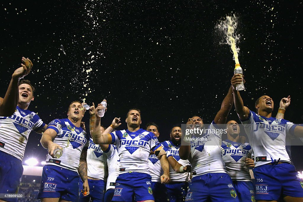 The Bulldogs team sing their team song in front of the crowd on the hill as they celebrate victory during the round 16 NRL match between the Canterbury Bulldogs and the Melbourne Storm at Belmore Sports Ground on June 29, 2015 in Sydney, Australia.