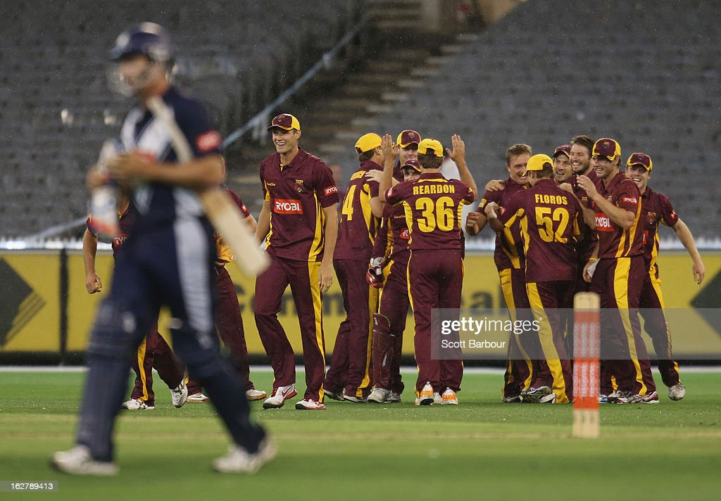The Bulls celebrate after winning the Ryobi One Day Cup final as the Fawad Ahmed of the Bushrangers leaves the field after being dismissed after the Ryobi One Day Cup final match between the Victorian Bushrangers and the Queensland Bulls at Melbourne Cricket Ground on February 27, 2013 in Melbourne, Australia.