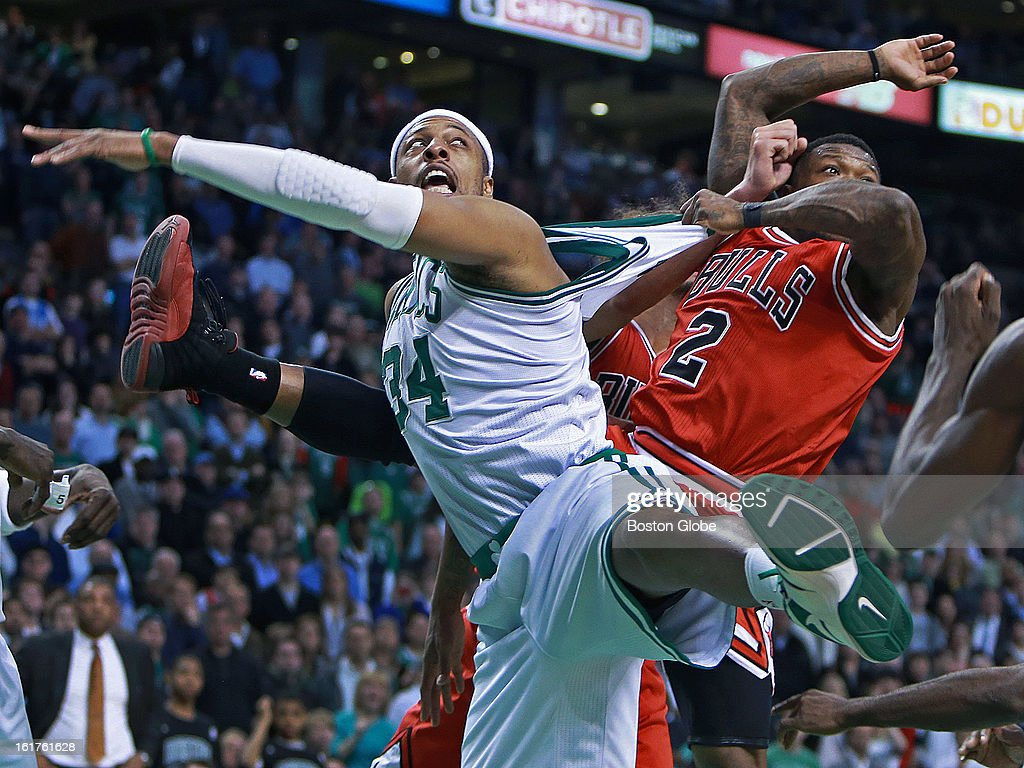 The Bulls' Nate Robinson, right, has a good grip on Celtics captain Paul Pierce, left, as he stretches his jersey as they battle under the boards and eye the bouncing ball during the final frantic seconds of the game as the Boston Celtics hosted the Chicago Bulls in an NBA regular season basketball game at the TD Garden.