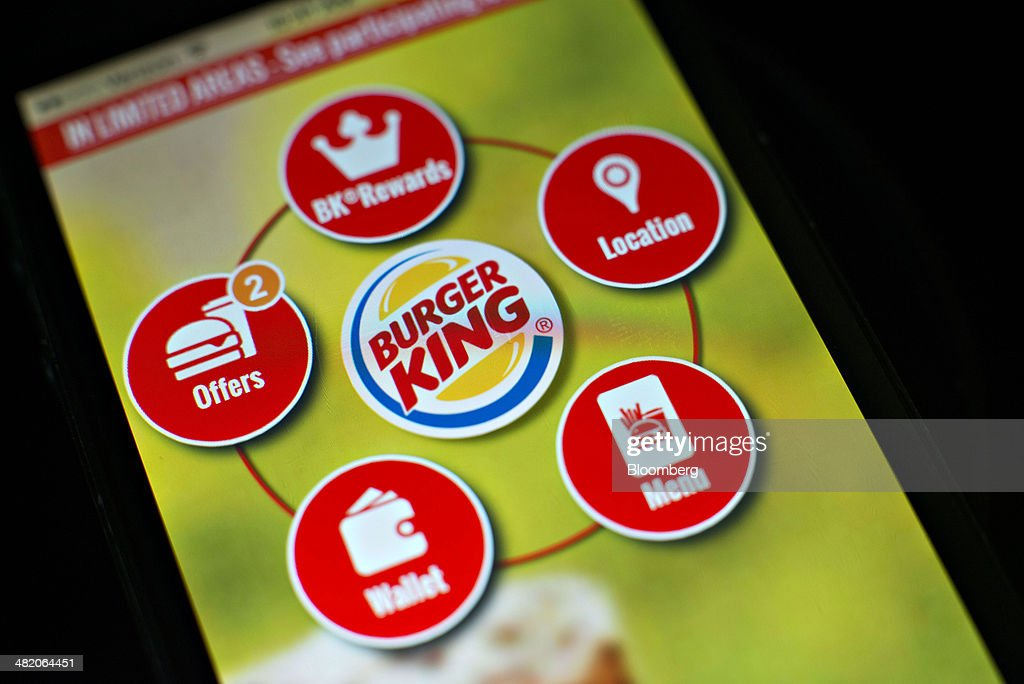 The Burger King Worldwide Inc. app is displayed for a photograph on an Apple Inc. iPhone 5 in Tiskilwa, Illinois, U.S., on Wednesday, April 2, 2014. Burger King Worldwide Inc., the second-biggest U.S. burger chain by store count, is introducing an application that will allow customers to pay for Whoppers with their smartphones as it races rivals to woo younger diners. Fast-food chains including McDonalds Corp. and Dunkin Brands Group Inc. are competing to quickly introduce the best loyalty programs and smartphone apps to try to attract millennials and teens. Photographer: Daniel Acker/Bloomberg via Getty Images