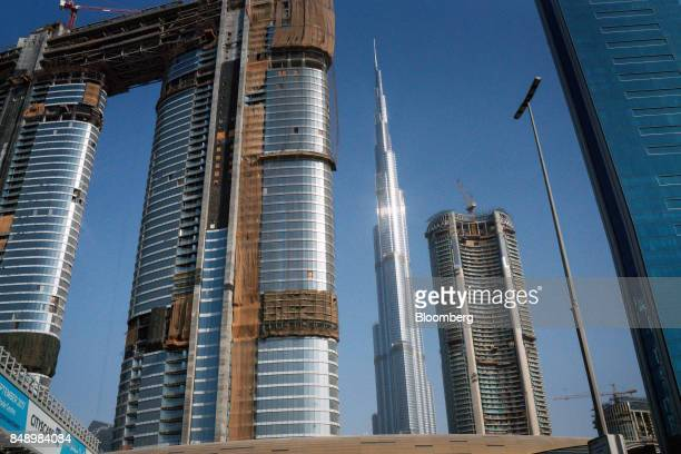 The Burj Khalifa skyscraper center stands on the city skyline beyond new skyscrapers under construction in Dubai United Arab Emirates on Tuesday Sept...