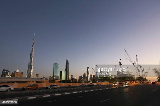 The Burj Khalifa tower left and construction cranes stand on the city skyline at dusk in Dubai United Arab Emirates on Sunday Nov 9 2014 A year ago...