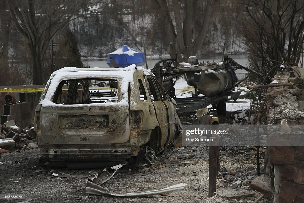 The burned out shell of a car sits in the rubble at the site of the Christmas eve shooting and fires on Wednesday, December 26, 2012 in Webster, New York. Law enforcement officials have not publicly identified which gun or guns were used to shoot the four firefighters, two of them fatally, or in what authorities have described as a brief standoff between William Spengler Jr., and a Webster police officer on Christmas eve.