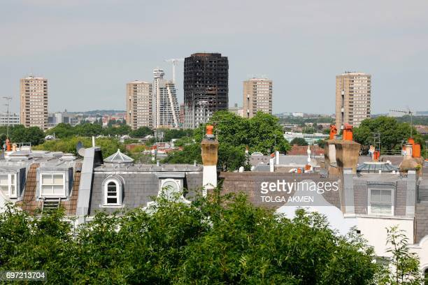 The burned shell of Grenfell Tower block is seen in the background behind town houses in Notting Hill west London on June 18 2017 The presumed death...
