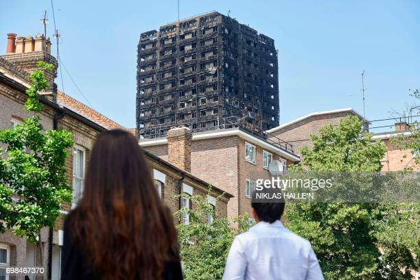TOPSHOT The burnedout shell of the Grenfell Tower block is seen behind terraced houses as local residents look on near the scene of the fire in North...